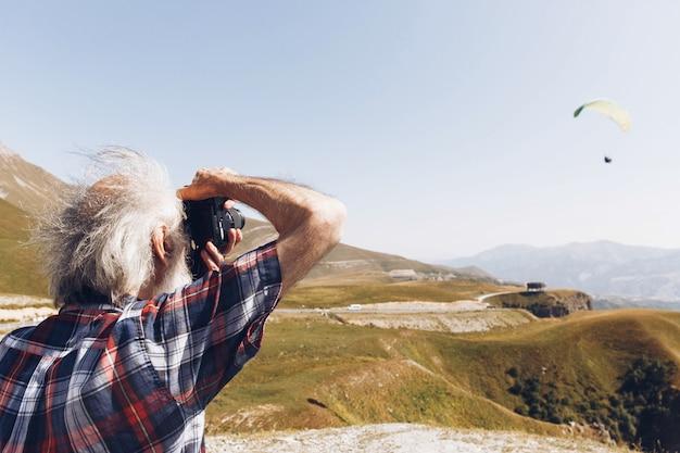 Alter mann macht ein bild eines fallschirms im himmel über georgischen bergen
