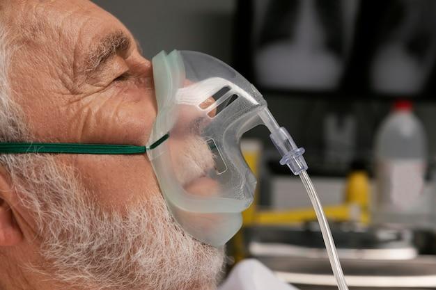 Alter mann mit beatmungsgerät in einem krankenhausbett