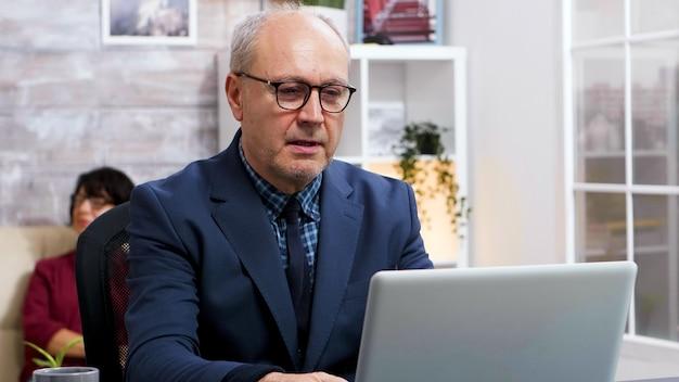 Alter mann mit brille am laptop im wohnzimmer arbeiten. alte frau sitzt auf dem sofa im hintergrund.