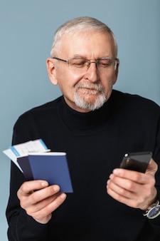 Alter mann mit flugtickets und passporträt