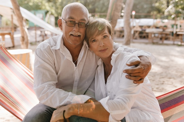 Alter mann mit grauem schnurrbart und brille im hemd, das in kamera schaut und blonde kurzhaarige frau in weißen kleidern am strand umarmt.