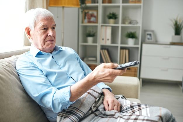 Alter mann mit kariertem plaid, der auf couch sitzt und knöpfe auf fernbedienung drückt, während man zu hause fernsieht