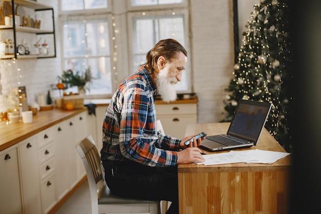 Alter mann mit laptop. großvater sitzt in einer weihnachtsdekoration. mann mit handy.