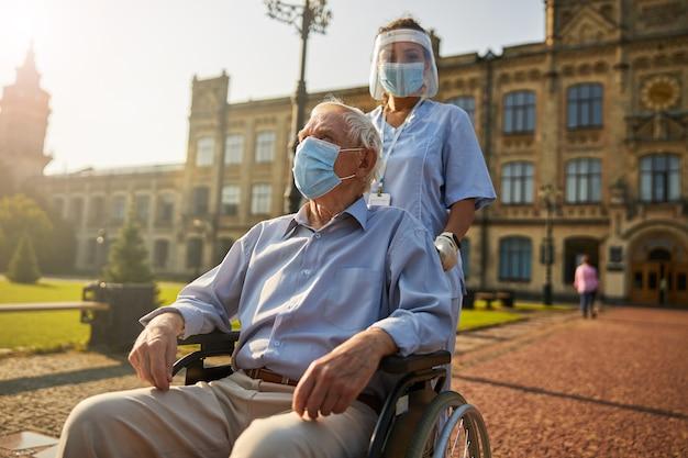 Alter mann mit maske beim sitzen im rollstuhl im hof