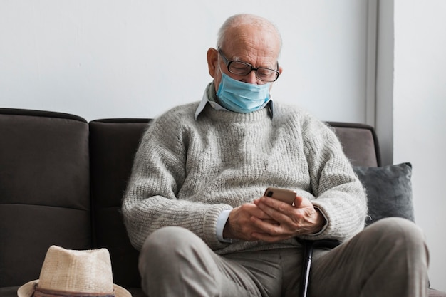Alter mann mit medizinischer maske in einem pflegeheim unter verwendung des smartphones