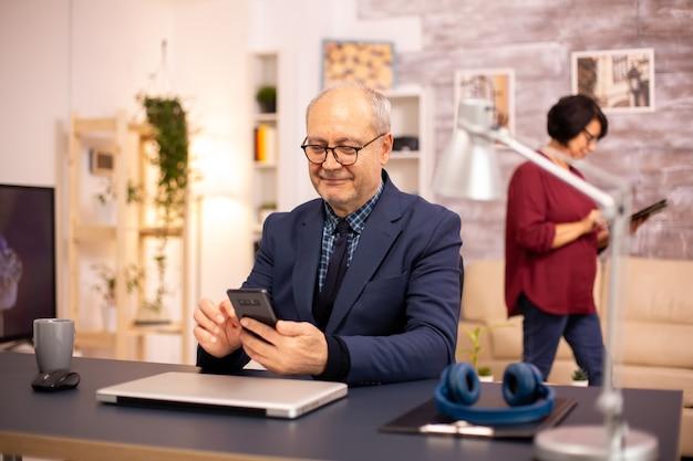Alter mann mit neuer technologie im gemütlichen haus. er hat ein smartphone in der hand