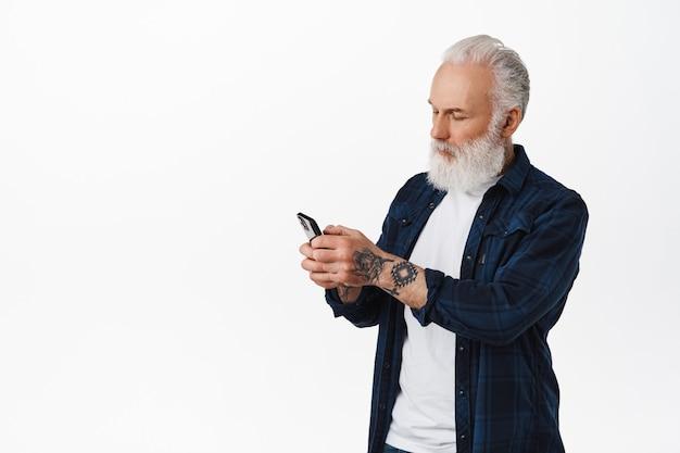 Alter mann mit tätowierungen und bart-messaging, handy-bildschirm beiläufig lesend, handy benutzend, über weißer wand stehend.