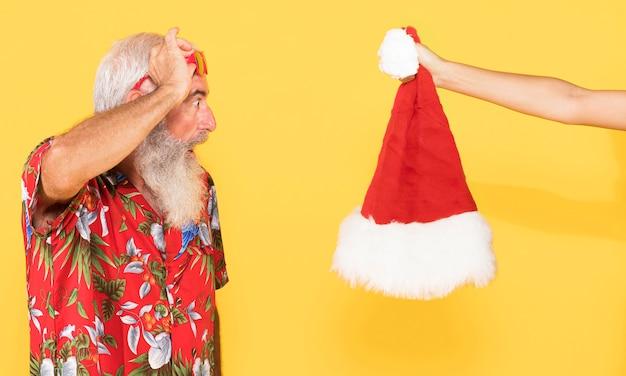 Alter mann mit tropischem hemd und weihnachtsmütze