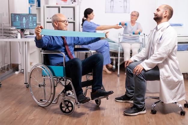 Alter mann nach therapie mit hilfe von medizinischem personal im modernen krankenhaus