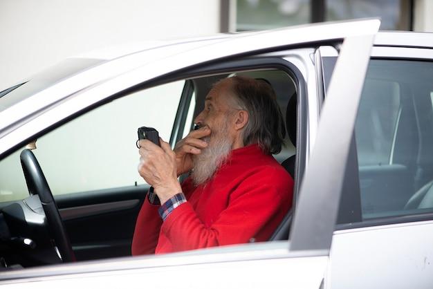 Alter mann senior mit grauem bart sitzt im auto und hält eine vintage-fotokamera