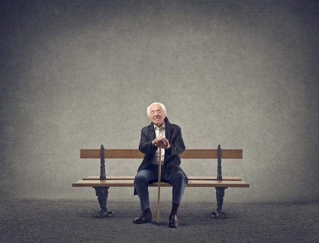 Alter mann sitzt auf einer bank