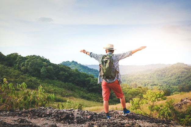 Alter mann trägt einen rucksack, wandert und steht auf einem hohen berg er ist glücklich. senioren-reisekonzept