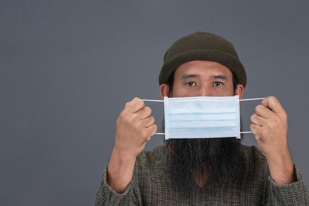 Alter mann trägt maske, während auf schwarzer wand stehend.