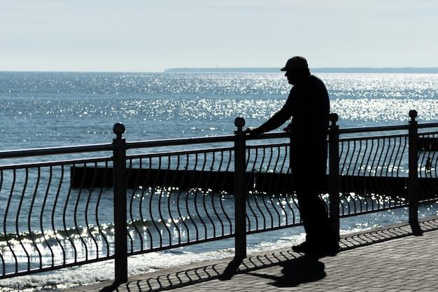 Alter mann träumt von lebensabenteuer, vorbei an reisen und schaut aufs meer. hintere hintere ansicht, kopienraum. alter krebswitwer vermisst seine frau. sonniges wetter und sauberes blaues meer.