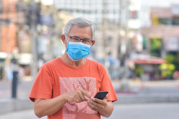 Alter mann tragen chirurgische maske, die handy in straßenstadt hält, neue normale maske schützt coronavirus covid19