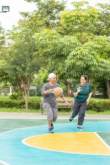 Alter mann und frau, die im bangyai park nonthaburi so glücklich basketball spielen