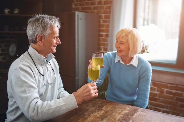 Alter mann und frau sitzen zusammen in der küche und trinken