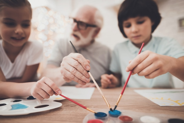 Alter mann und kinder halten pinsel zusammen malen.