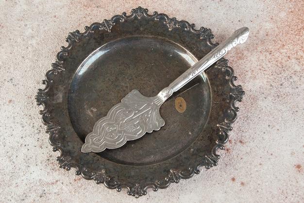 Alter metallkuchenspatel in der antiken platte auf betontisch.
