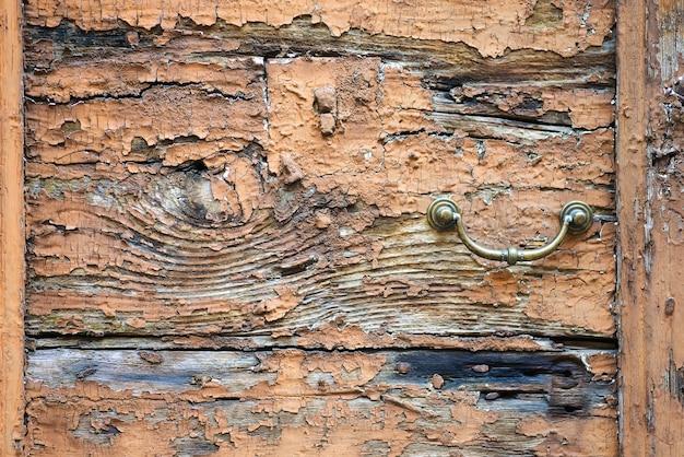 Alter metalltürgriffklopfer auf einem rauen hölzernen hintergrund
