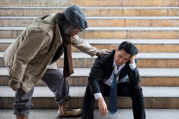 Alter obdachloser bettler jubelt gestressten geschäftsmann in der stadt auf. arbeitsloser mann aus den 40ern wird aufgrund einer covid-19-delta-pandemie entlassen. lebenskrise aufgrund von krankheit.