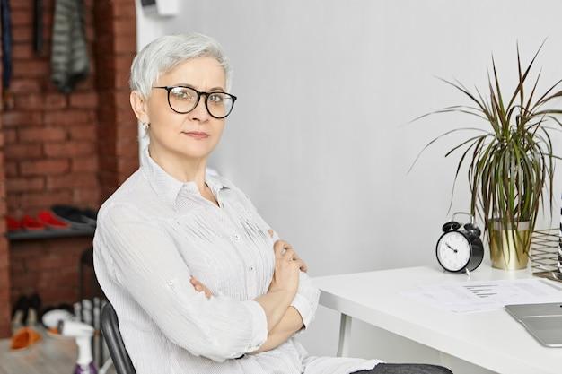 Alter, reife, beruf und beschäftigung. innenaufnahme einer selbstbewussten, ernsthaften, fünfzigjährigen freiberuflerin, die zu hause im büro arbeitet, während sie im ruhestand ist, einen laptop benutzt und die arme auf ihrer brust verschränkt