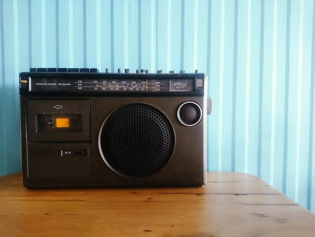 Alter retro- kassettenradioklassiker auf tabelle mit blauer wand
