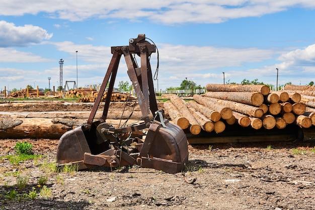 Alter rostiger greifeimer des baggers im hof einer holzbearbeitungsfabrik