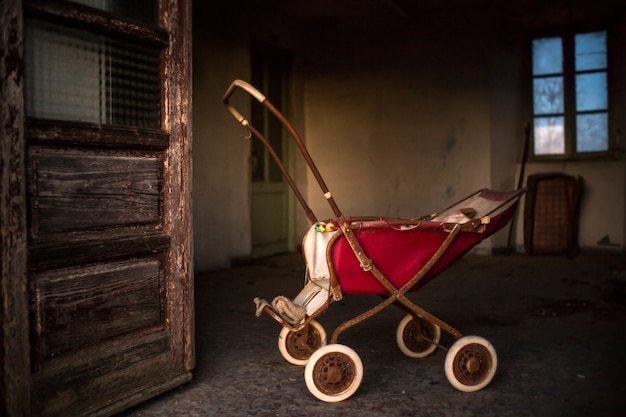 Alter rostiger kinderwagen innerhalb eines gebäudes mit verwitterten türen und fenstern