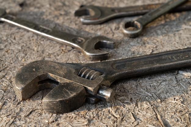 Alter rostiger verstellbarer schraubenschlüssel und schraubenschlüssel auf hölzernem hintergrund.