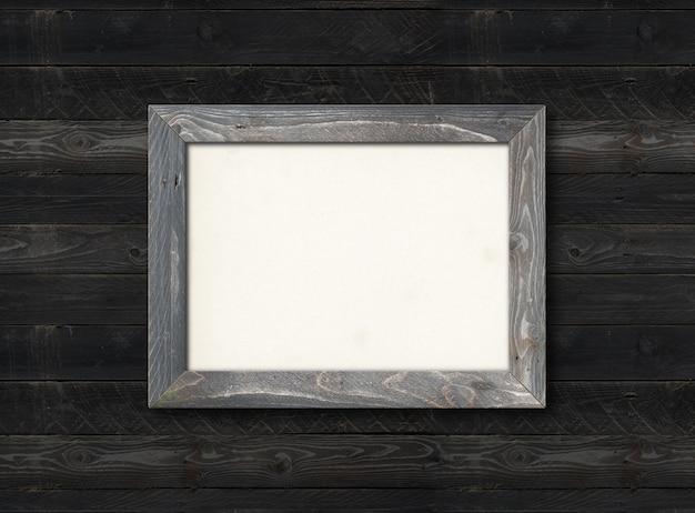 Alter rustikaler hölzerner bilderrahmen, der an einer schwarzen holzwand hängt. horizontales bild. leere modellvorlage