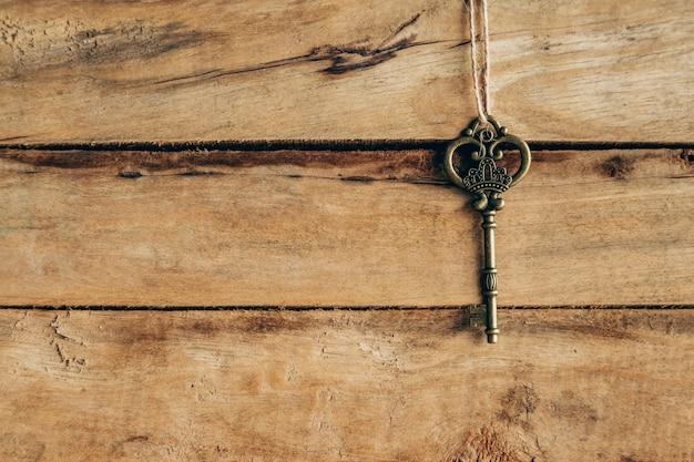 Alter schlüssel, der am braunen holz mit platz hängt.