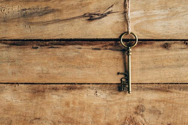 Alter schlüssel, der an braunem holz und liebeskonzept hängt.