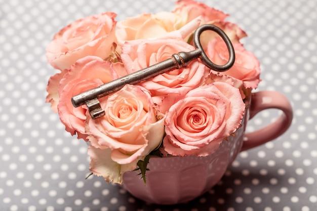 Alter schlüssel über rosa rosen in einer tasse. vintage-dekor