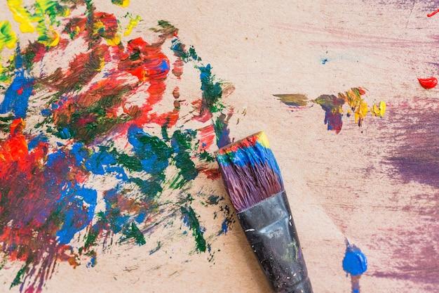 Alter schmutziger malerpinsel und mehrfarbige unordentliche gemalte oberfläche