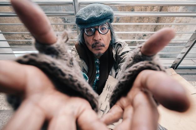 Alter schmutziger obdachloser streckt die hände nach vorne aus und schaut