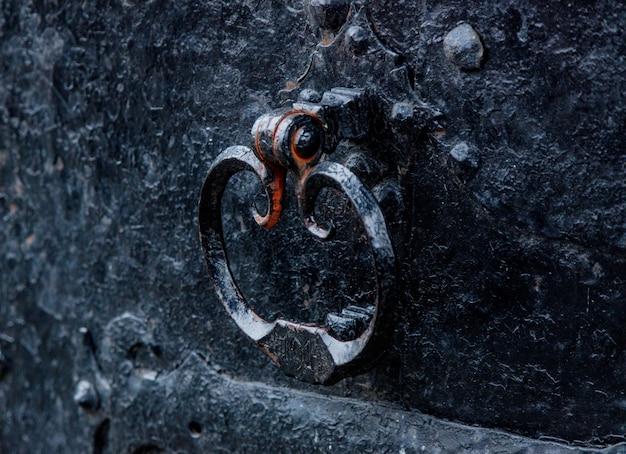 Alter schwarzer metallknopf einer alten tür in gealterter mittelalterlicher burg