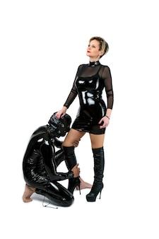 Alter spielen bdsm fetisch sexspiele mit herrin und sklave. mann kniet vor seiner frau, isoliert auf weiß. der sklave senkte die knie und den kopf. dominieren gehorchen und ausziehen verführen einen partner.