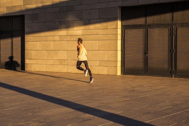 Alter sportler, der auf landstraße läuft