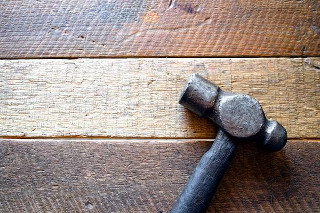 Alter stahlhammer auf holzhintergrund. draufsicht. flach liegen