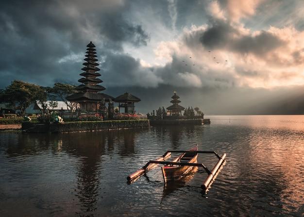Alter tempel von pura ulun danu bratan mit traditionellem boot auf bratan see, bali bei sonnenaufgang