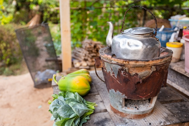 Alter thailändischer kessel auf thailändischem holzkohlenofen mit grünem blattgemüse und papaya gesetzt