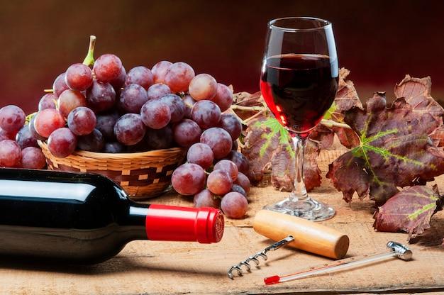 Alter tisch mit einer flasche wein, weinblättern und roten trauben