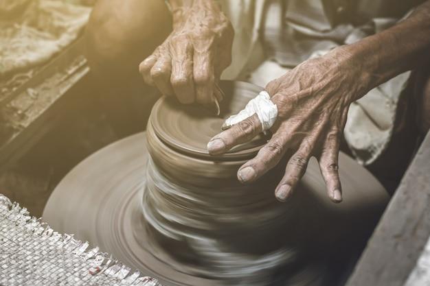 Alter töpfer, der schüssel in der tonwarenarbeit macht. alter mann, der lehm mit handwerk formt.