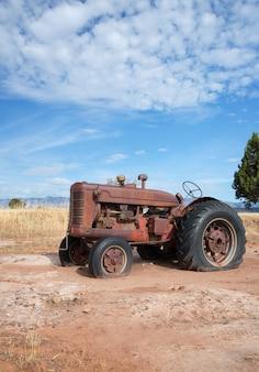 Alter traktor in der ländlichen landschaftsvertikale