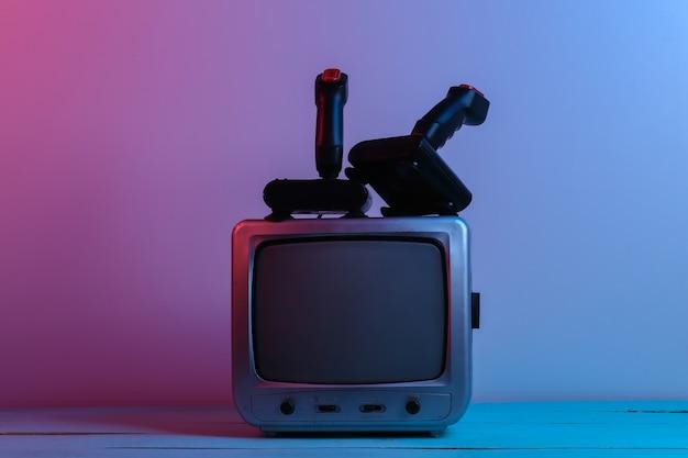 Alter tv-empfänger mit retro-joysticks in rot-blauem neonlicht. retro-spiele