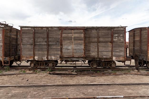Alter und rostiger hölzerner eisenbahnwagen verlassen auf einer eisenbahnstrecke. bolivien