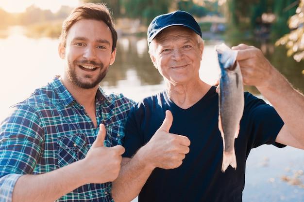 Alter vater mit dem bärtigen sohn, der auf fluss fischt.