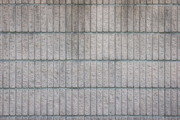 Alter verwitterter schmutziger vertikaler zementziegelsteinblockstapelwand-beschaffenheitsoberflächenhintergrund.