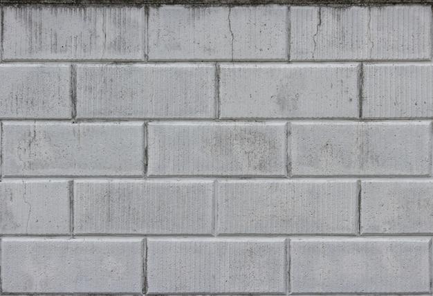 Alter verwitterter schmutziger zementbacksteinblockmauerbeschaffenheits-oberflächenhintergrund.